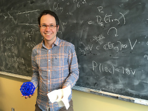 Joel Kamnitzer in front of a black board holding math objects